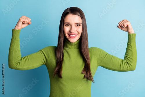 Fototapeta Photo of positive lovely cute lady hands showing biceps wear green turtleneck is