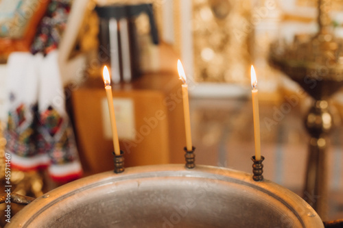Burning candles on a baptismal font in the church Fototapet