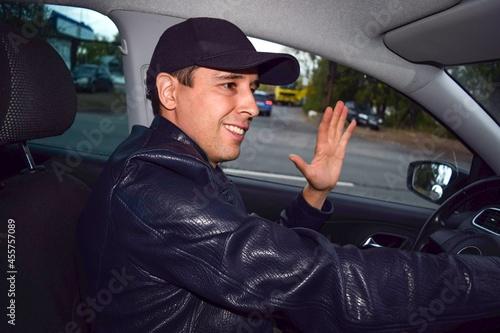 A young man behind the wheel waves and smiles on an autumn evening Tapéta, Fotótapéta