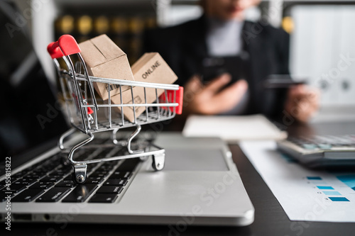 Canvas Close up of mini shopping cart with small parcel box on laptop keyboard and businesswomen purchasing online via credit card in the background, e-commerce, business online concept