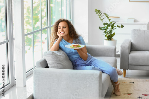 Young African-American woman with tasty sandwich at home