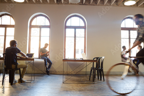 Slika na platnu Casual businessman riding bicycle in open office