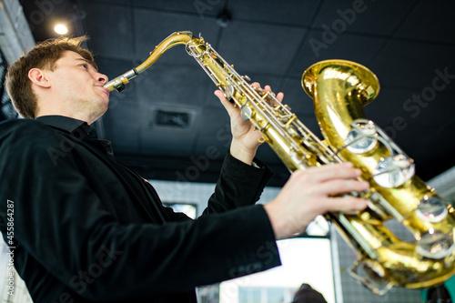 Obraz na płótnie Male jazz musician playing a saxophone in a restaurant