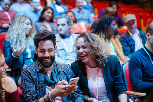Man and woman with smart phone in conference audience Fototapet