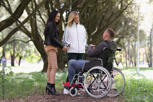 Man in wheelchair and laughing woman chatting in park Fotobehang