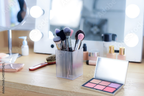 Fotografiet Powder set without foundation or pressed powder color gradation in square, makeup brushes and skin creams, on the dressing table with a mirror