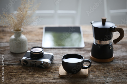 Fotografering Black coffee cup and moka pot with camera and tablet on wooden table