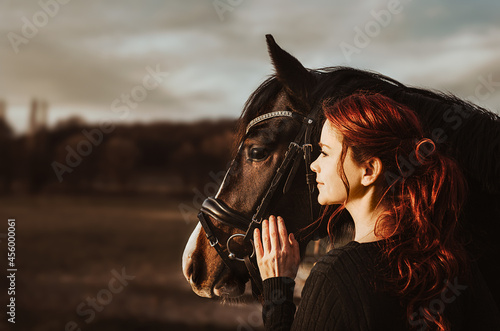 Canvastavla 2 heads one love! stallion with head collar and redhead woman are bonding while
