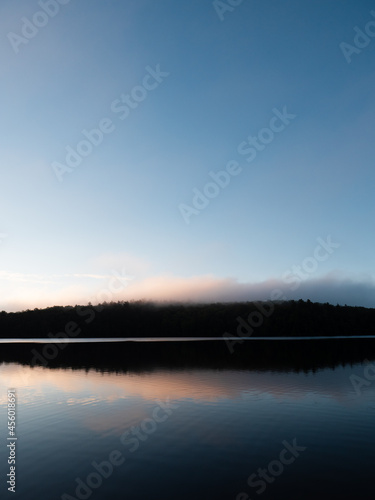 Fotografiet Dawn over a lake and a forested hillside in New Hampshire
