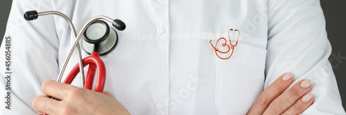 Doctor with brooch on uniform holding stethoscope closeup Fotobehang