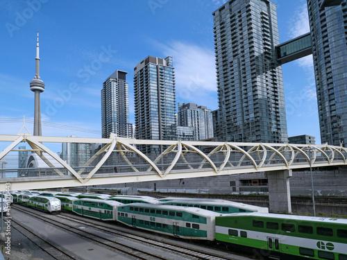Fototapeta premium Pedestrian bridge above a rail corridor in downtown Toronto, with commuter trains.