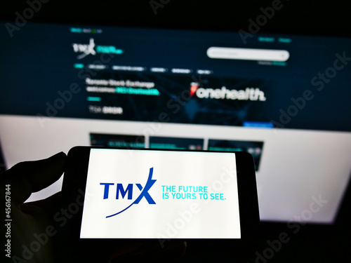 Fototapeta premium STUTTGART, GERMANY - Mar 07, 2021: Person holding smartphone with logo of company TMX Group Limited on screen in front of website.
