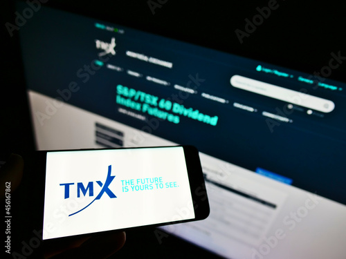 Fototapeta premium STUTTGART, GERMANY - Mar 07, 2021: Person holding cellphone with logo of company TMX Group Ltd on screen in front of web page.