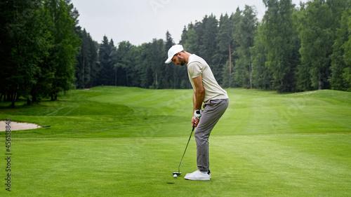 Fototapeta premium Young golfer in uniform playing golf