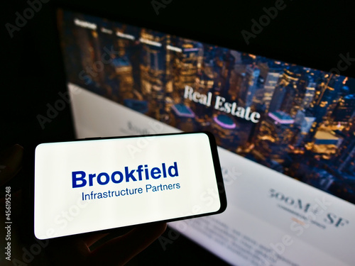 Fototapeta premium STUTTGART, GERMANY - Mar 05, 2021: Person holding smartphone with logo of Brookfield Infrastructure Partners LP on screen with website.
