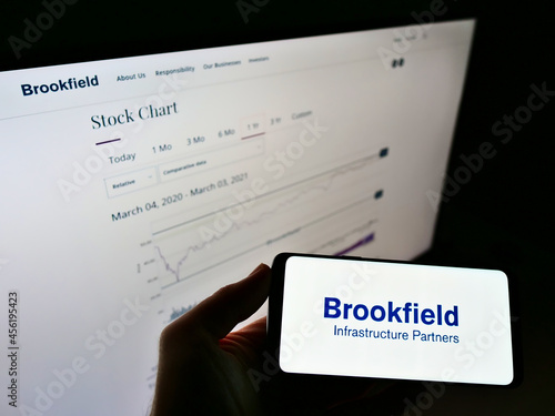 Fototapeta premium STUTTGART, GERMANY - Mar 05, 2021: Person holding cellphone with logo of Brookfield Infrastructure Partners on screen with webpage.