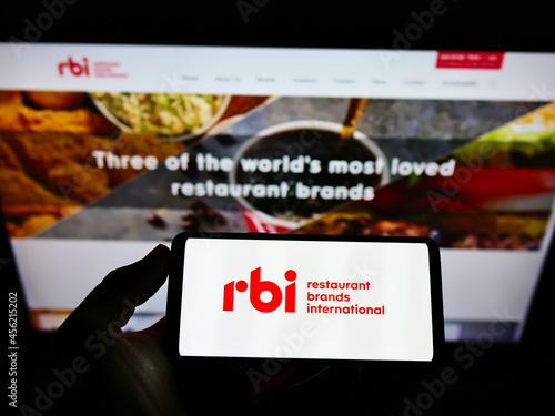 Fototapeta premium STUTTGART, GERMANY - Mar 03, 2021: Person holding cellphone with logo of Restaurant Brands International Inc. (RBI) on screen.
