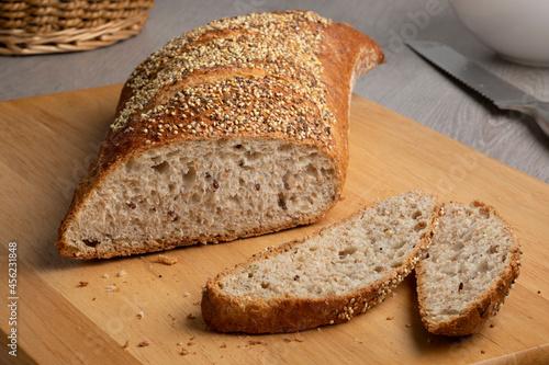 Billede på lærred Sliced traditional sourdough loaf of bread in a special shape with seeds on a cu