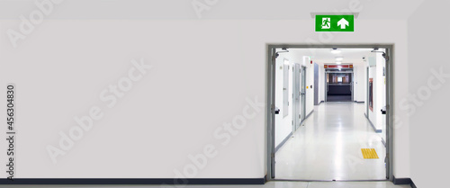 Fotografiet Green emergency fire exit sign or fire escape on ceiling for doorway or door exit in the building for evacuation in the event of a fire and safety prevent or prevention and rescue