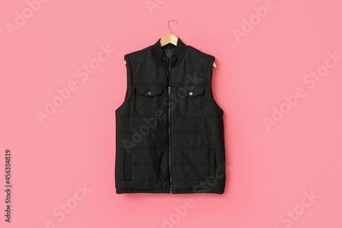 Hanger with vest jacket on color background Fototapeta