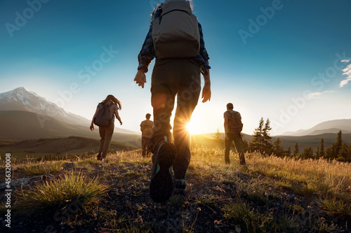 Obraz na plátne Group of sporty people walks in mountains at sunset with backpacks