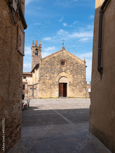 Fototapeta premium View from a Narrow Street in front of the Bell tower and the Church of Santa Maria Assunta in Piazza Roma in Monteriggioni, Siena - Italy