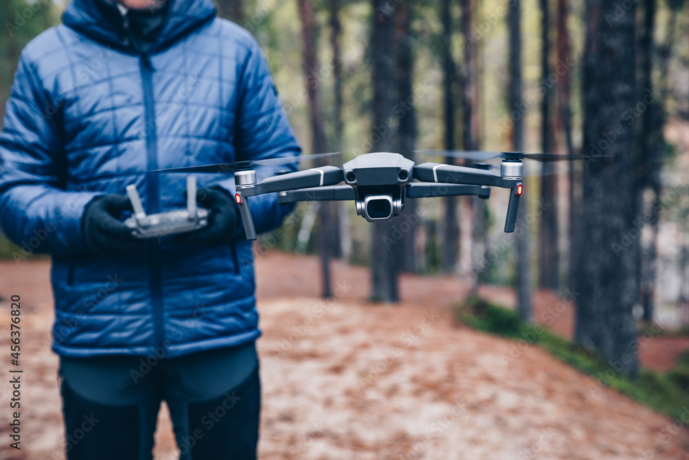 Man navigating a flying drone in the forest.