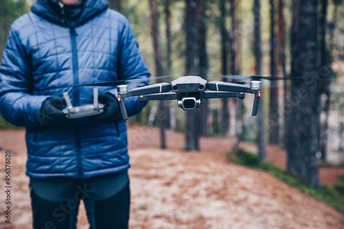 Fototapeta premium Man navigating a flying drone in the forest.