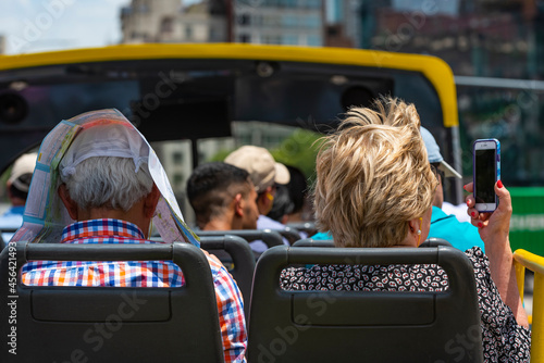 Fotografiet Back view of tourists, a man cover head with a paper, women with telefon rides o
