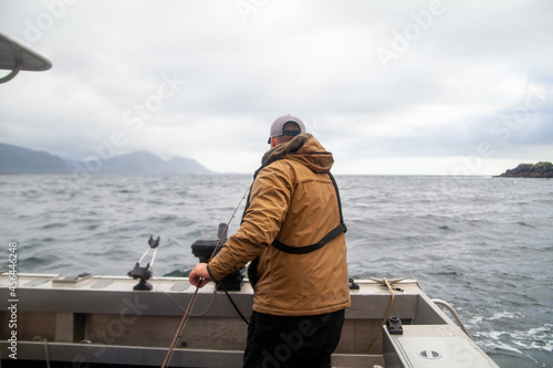 Murais de parede A man stands by a rod holder on a fishing charter boat in Winter Harbour, British-Columbia