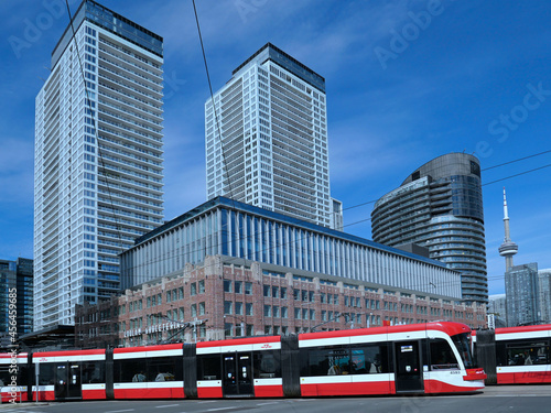 Fototapeta premium Toronto, Canada - A modern articulating streetcar or tram bends to go around a corner, with high rise apartment buildings in the background