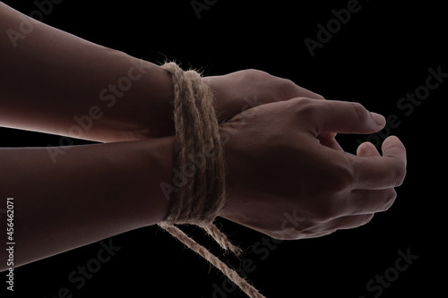Tablou Canvas Person hands tied with rope isolated on black dark background, captive victim re