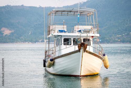Fotografia White pleasure boat navigating the waters of a Pacific ocean beach