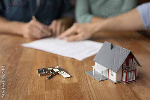 Crop close up of keys and small house carton mock-up model on table in real estate agent office. Couple buyer sign document make deal close agreement in background, buy home together. Rent concept.