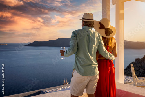 A romantic couple stands on the balkony and enjoys the beautiful summer sunset o Fotobehang