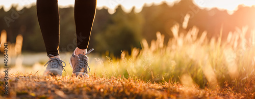 Foto Woman with sports shoe and leggings jogging in nature during sunset