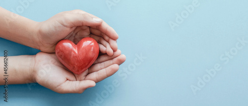 Fotografiet hands holding red heart on blue background, health care, love, organ donation, f