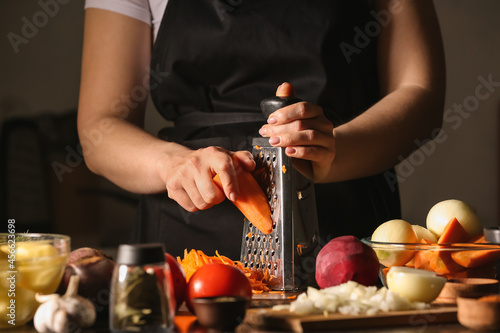 Woman grating carrot for delicious borscht in kitchen