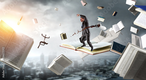 Photo Businessman balancing on top of the flying book . Mixed media