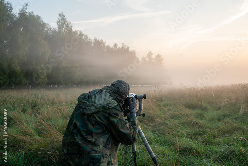 Stampa su Tela Nature photographer standing in camouflage clothing with a camera on a tripod