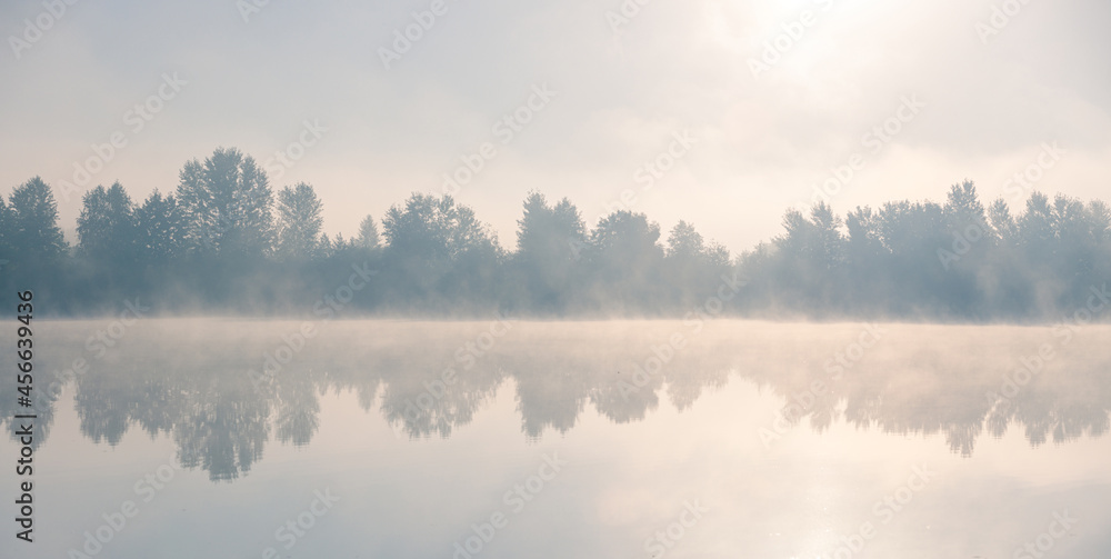 Beautiful foggy morning. Lake coast trees symmetrically reflect in the river water. Fog over autumn lake water.
