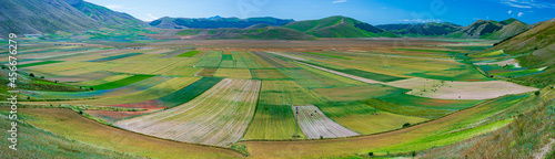 Fotografia Castelluccio di Norcia highlands, Italy, blooming cultivated fields, tourist famous colourful flowering plain in the Apennines