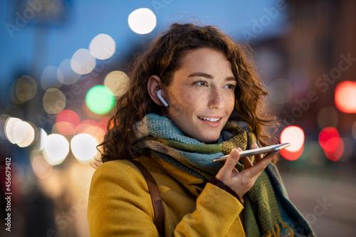 Woman sending voice note on city street in winter night