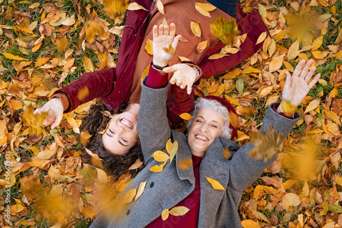 Fototapeta Grandmother and granddaughter lying on foliage and enjoy the autumn