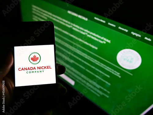 Fototapeta premium STUTTGART, GERMANY - Feb 16, 2021: Person holding mobile phone with logo of Canada Nickel Company Inc. on screen in front of web page.