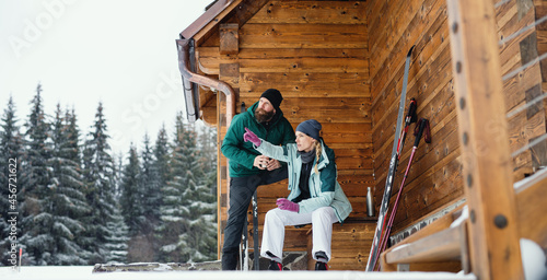 Fotografiet Mature couple resting by wooden hut outdoors in winter nature, cross country skiing