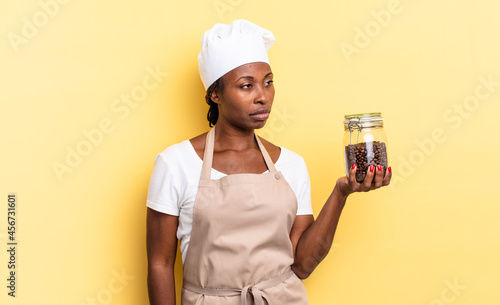 Obraz na plátně black afro chef woman feeling sad, upset or angry and looking to the side with a negative attitude, frowning in disagreement