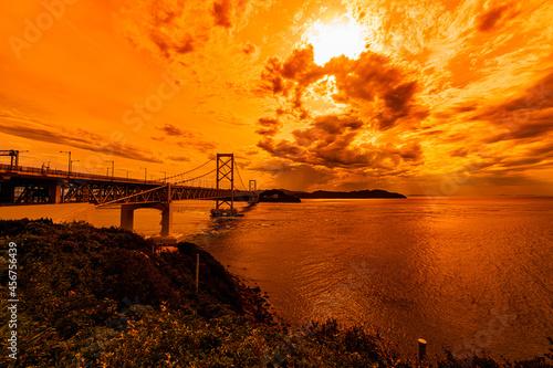 Obraz na plátně Naruto Kaikyo Ohashi bridge in the background of sunset orange color sky