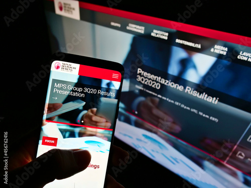 Fototapeta premium STUTTGART, GERMANY - Feb 11, 2021: Person holding smartphone with web page of Banca Monte dei Paschi di Siena on screen with monitor.