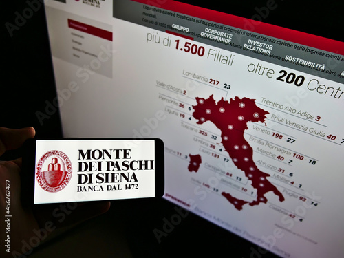 Fototapeta premium STUTTGART, GERMANY - Feb 11, 2021: Person holding smartphone with logo of Banca Monte dei Paschi di Siena (BMPS) on screen with webpage